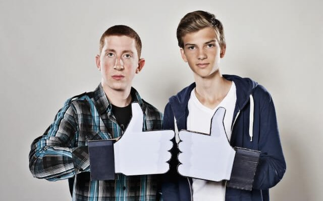 male teens holding fake like button