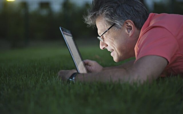 A mature man lying in the grass using a laptop
